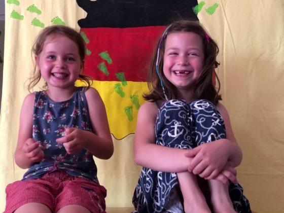 Zwei Mädchen sitzen auf einem kleinen Tisch, hinter ihnen eine Deutschlandkarte