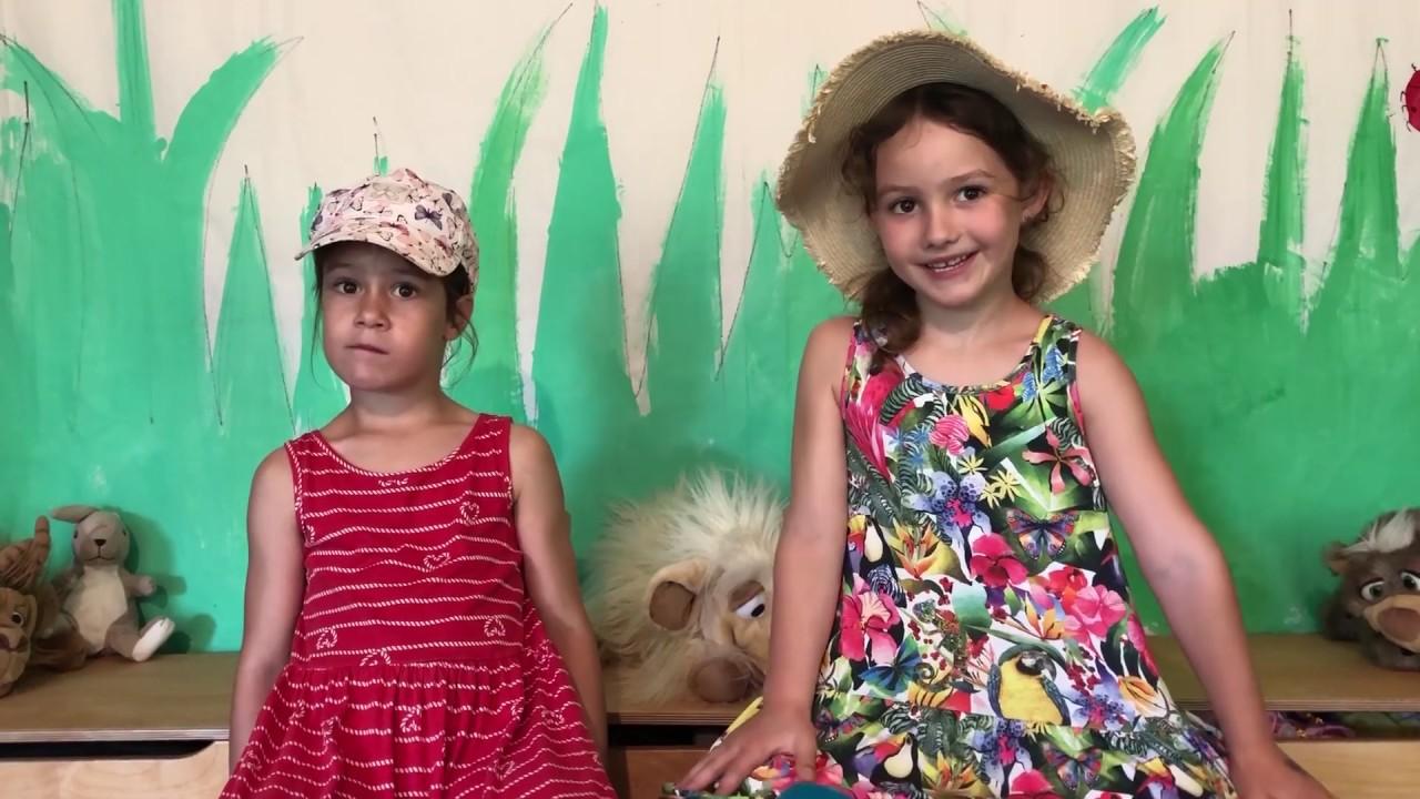 Zwei kleine Mädchen sitzen auf Kinderstühlen