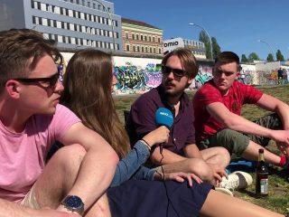 Eine junge Frau interviewt drei Männer auf einer Wiese