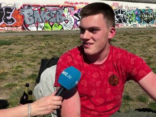 Ein junger Mann sitzt auf einer Wiese und spricht in ein Mikrofon