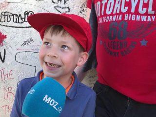 Ein kleiner Junge spricht in ein Reporter-Mikrofon