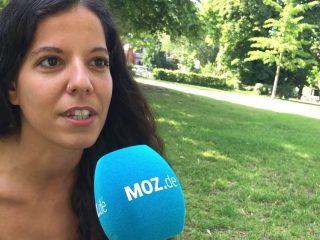 Eine Frau sitzt auf einer Wiese und spricht in ein Mikrofon
