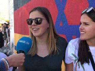Zwei junge Frauen vor einem bemalten Stück der Berliner Mauer