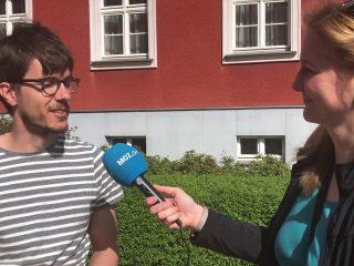 Eine Frau interviewt mit einem Mikrofon einen Passanten