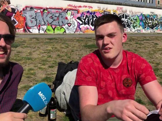 Zwei junge Männer sitzen auf einer Wiese
