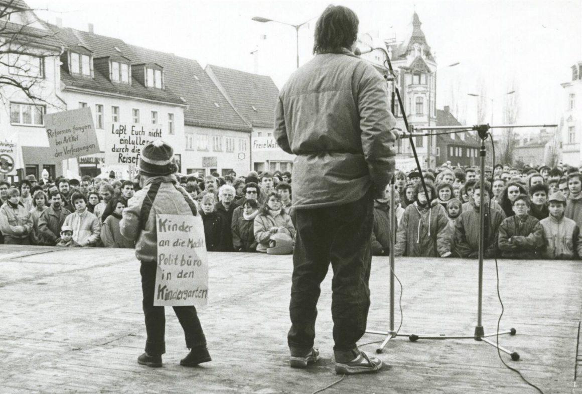 """Kurz nach dem Mauerfall steht der damalige Jugendpfarrer Michael Wolf mit seinem damals vierjährigen Sohn Richard in Finsterwalde auf der Bühne. Seine Bitte damals: """"Bewahren Sie Ruhe und bleiben Sie kritisch."""""""