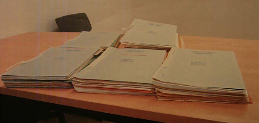 Auf einem Tisch liegen alte Papierstapel: Akten.