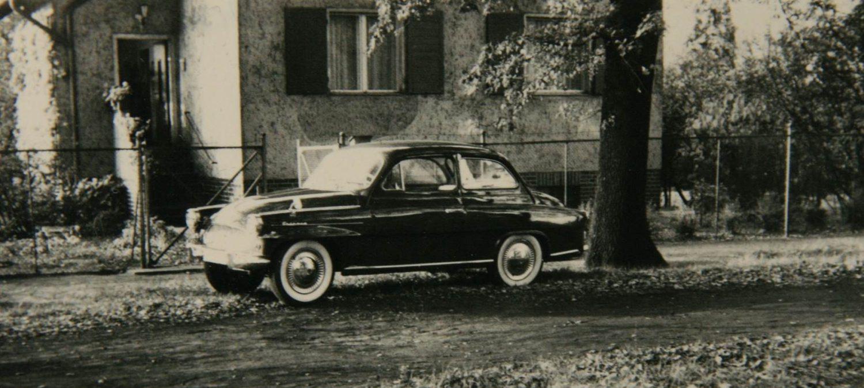 Ein dunkles Auto steht an der Straße vor einem Haus. Es liegen Blätter von Bäumen auf dem Boden. Es muss Herbst sein.