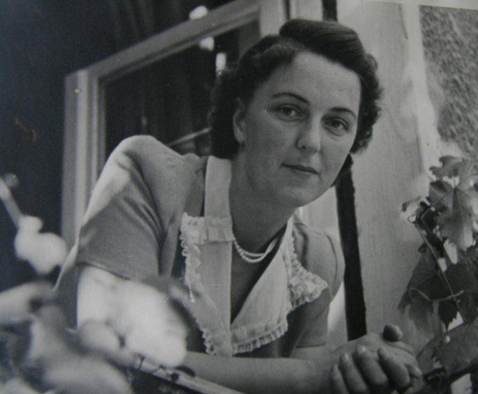 Auf dem Foto von 1955 lehnt sich Margarete Brauns auf beide Unterarme gestützt aus dem Fenster ihres Wohnhauses.