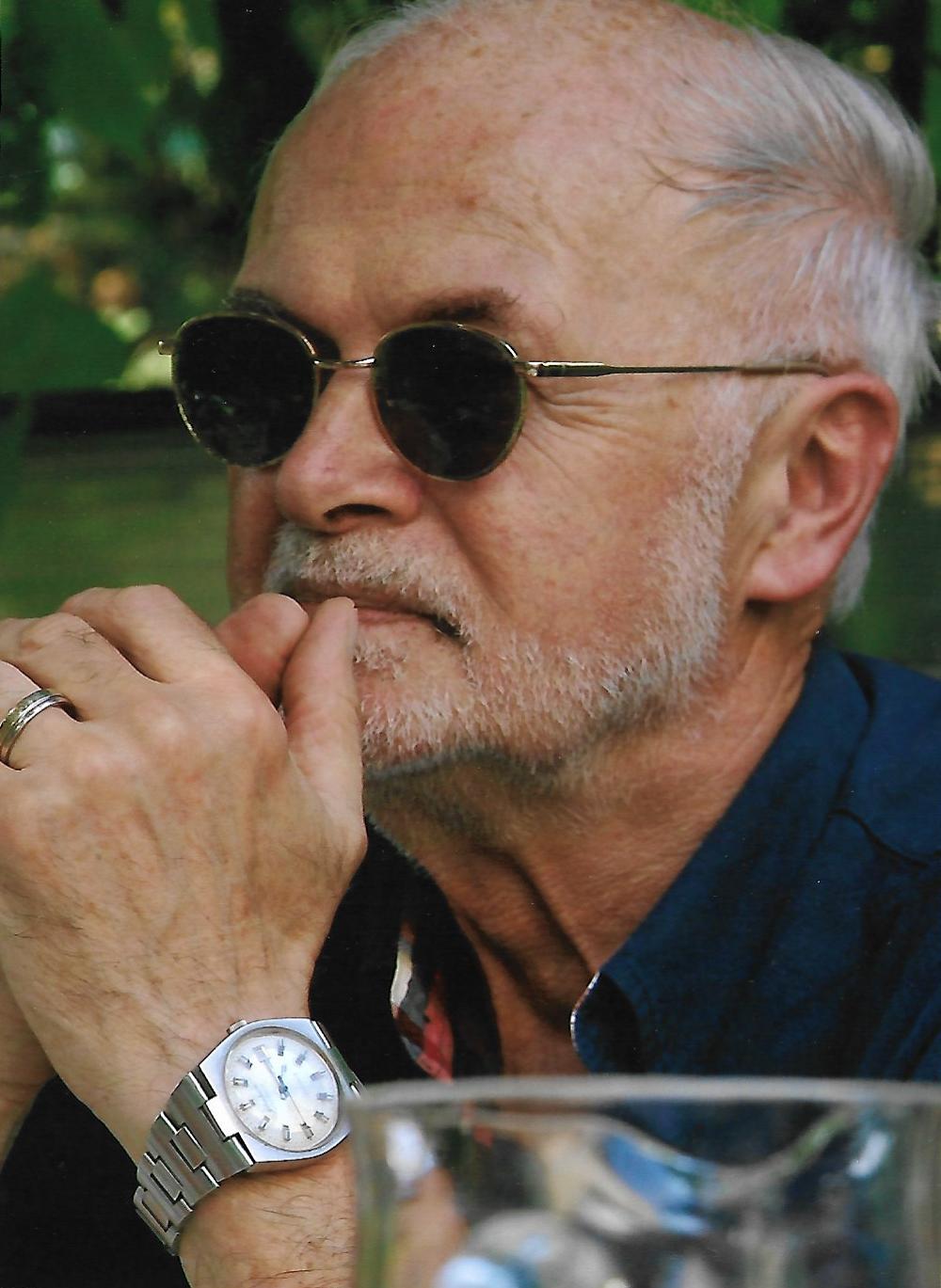 Der Kopf eines ältereren Mannes mit Sonnenbrille ist zu sehen. Er stützt sein Kinn nachdenklich auf seine ineinander verschränkten Hände und schaut seitlich aus dem Bild.