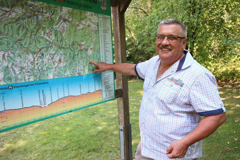 Rudi Siegmund steht im Jahr 2019 am Waldrand nahe Brennersgrün. Auf einer Karte zeigt er, wo er vor beinahe 50 Jahren in den Westen floh.